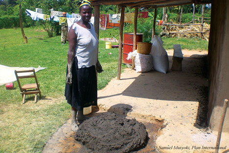 A woman in Siaya demonstrates how they use cow dung and mud to smear the pit latrines walls